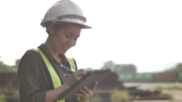 industrial engineer asian female in hard hat wearing safety jacket uses touchscreen tablet computer - using digital tablet stock videos & royalty-free footage