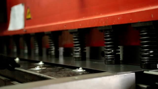 Industrial machine cuts metal.