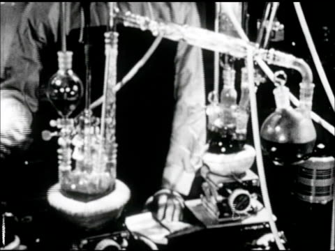 industrial machine turning in circular pattern ws male torso working w/ dark liquids in chemistry laboratory ms dark liquid being poured from beaker... - becher video stock e b–roll