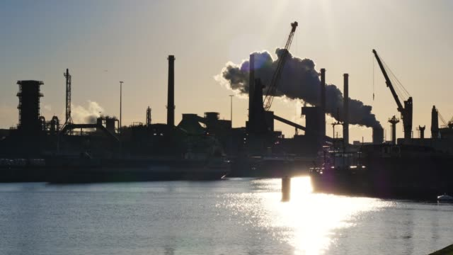 industrial plant with big smoke stacks and harbor - industry stock videos & royalty-free footage
