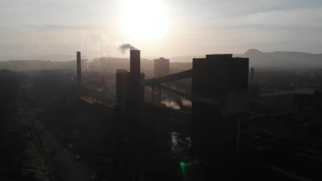 industrial plant with smoke stacks emitting pollution or steam into the atmosphere - fossiler brennstoff stock-videos und b-roll-filmmaterial