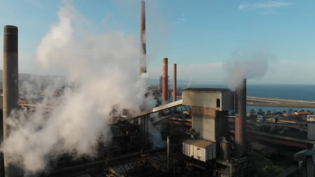 industrial plant with smoke stacks emitting pollution or steam into the atmosphere - 化石燃料点の映像素材/bロール