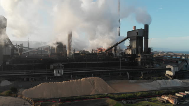 industrial plant with smoke stacks emitting pollution or steam into the atmosphere - coal stock videos & royalty-free footage