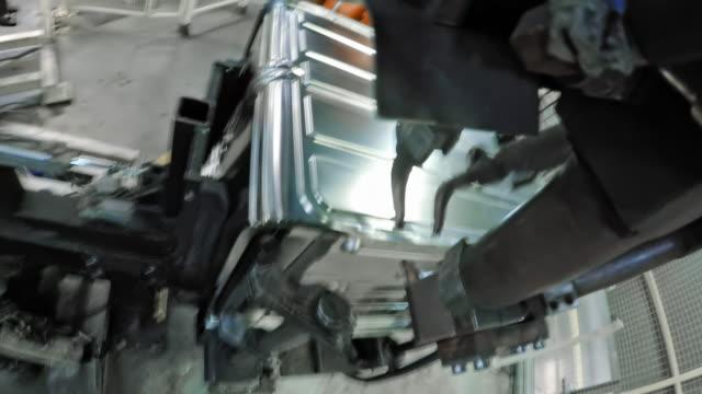 vidéos et rushes de robot industriel pov y attacher des pièces métalliques sur la base du produit - slovénie