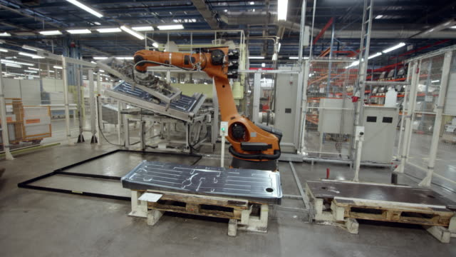 vídeos de stock e filmes b-roll de cs industrial robot moving molded aluminum plates in the factory - fabricar