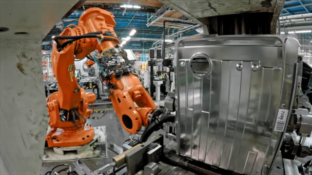 time lapse industrial robot taking a molded metal plate from the machine bending it - attrezzatura industriale video stock e b–roll