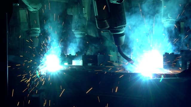 industrial robots are welding automotive part in factory - officina video stock e b–roll
