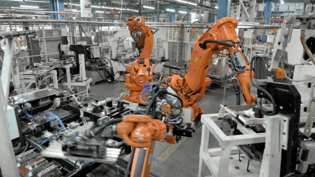 vídeos de stock e filmes b-roll de ld industrial robots assembling metal parts in a factory - automatizado