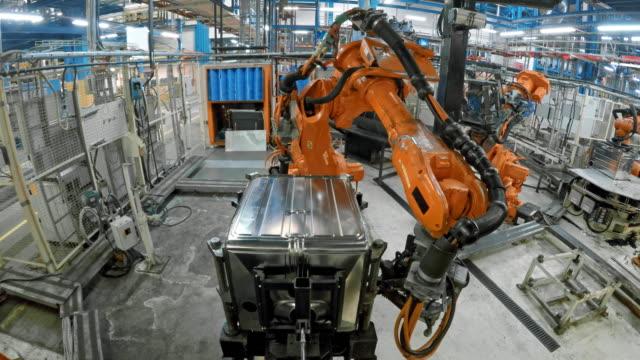 ld industrie roboter anbringen einen metallrahmen auf der basis eines produktes - halle gebäude stock-videos und b-roll-filmmaterial