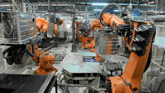 vídeos de stock e filmes b-roll de time-lapse industrial robots in operation in a factory - fábrica