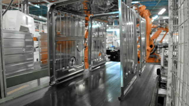 time-lapse industrial robots placing metal frames onto a conveyor belt - attrezzatura industriale video stock e b–roll