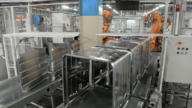 vidéos et rushes de time-lapse robots industriels, plaçant des objets métalliques sur un tapis roulant dans une usine - slovénie