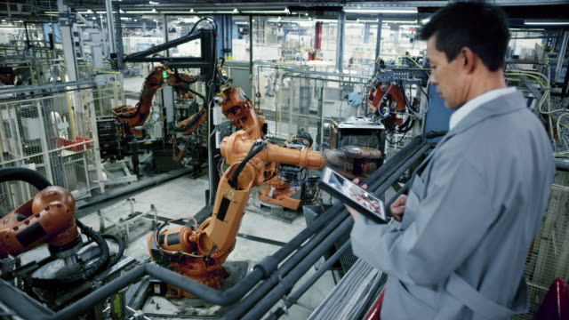 cs industrial robots' work process being supervised by an asian male engineer - attrezzatura industriale video stock e b–roll