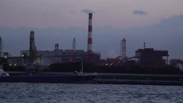 industrial ship unloading coal at the dock in front of coal power plant in japan - industrial district stock videos & royalty-free footage