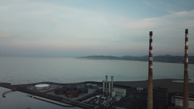 industrial skyline of dublin city across dublin bay with the incinerator and poolbeg chimney's in the view - marina stock videos & royalty-free footage