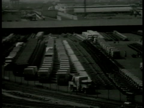 industrial smokestacks ha wwii munitions factory yard stockpiled goods vehicles trucks leaving gm general motors factory int factory w/ truck... - general motors stock videos & royalty-free footage
