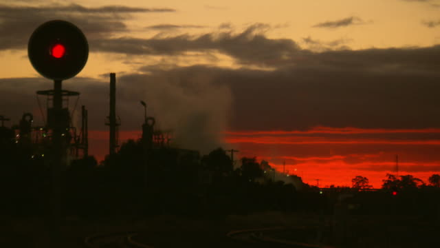 industrial sunset rail tracks with a stop light leads up to a wheat mill smoke stacks with smoke bellowing out - romantic sky stock videos & royalty-free footage