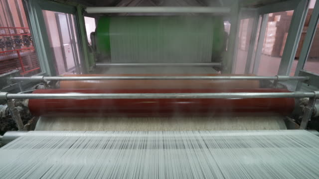 vídeos de stock e filmes b-roll de industrial warping and sizing machine in textile factory - textile