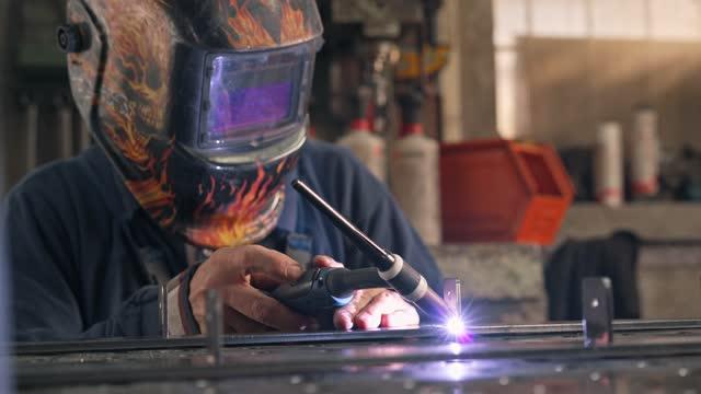 industrial welder connecting metal pieces together at his metal workshop - welding helmet stock videos & royalty-free footage
