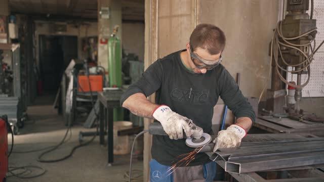 industrial welder grinding a metal bar in his welding workshop - welding helmet stock videos & royalty-free footage