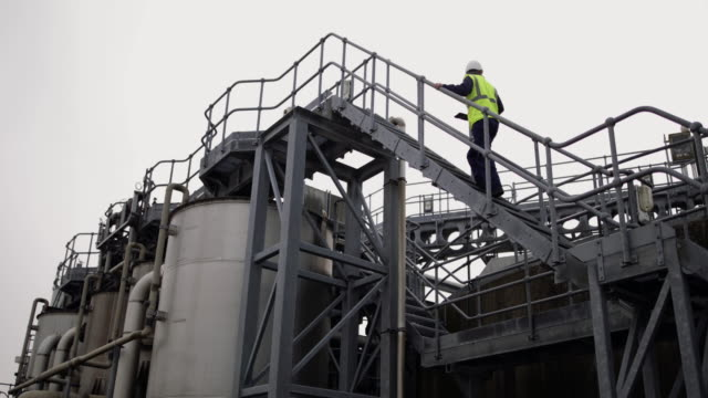 industrial worker climbing staircase using a digital tablet on site - tank stock videos & royalty-free footage