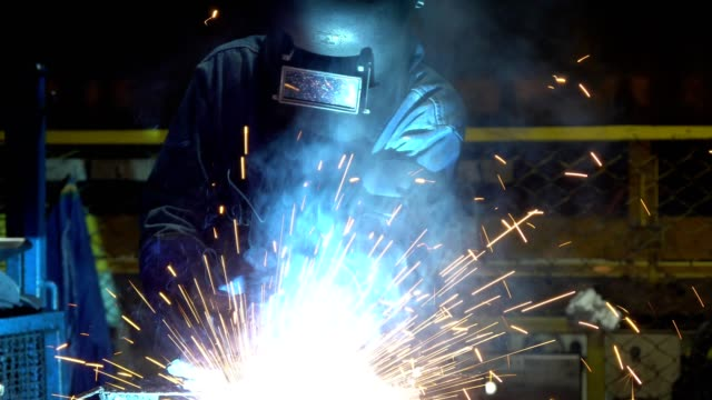 industrial worker is welding automotive part in car factory - metalwork stock videos & royalty-free footage