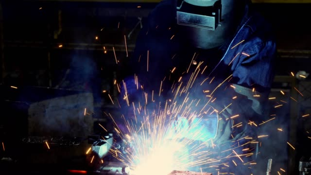 Industrial worker is welding in automotive part factory