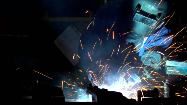 industrial worker is welding metal in production line with protective mask - arch stock videos & royalty-free footage
