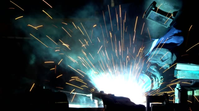 industrial worker is welding metal part in car factory - car plant stock videos & royalty-free footage