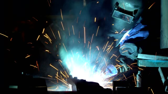 industrial worker is welding metal part in car factory with protective mask - car plant stock videos & royalty-free footage