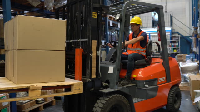 stockvideo's en b-roll-footage met industriële arbeider die vorkheftruck in pakhuis in werking stelt - hoofddeksel