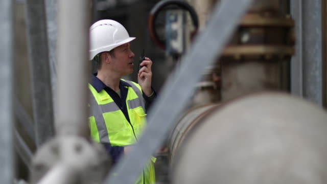 industrial worker using radio on site - fuel storage tank stock videos and b-roll footage