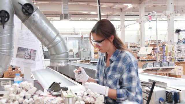 vídeos y material grabado en eventos de stock de trabajadora industrial mujer soldadura cables de equipos de fabricación en una fábrica - una mujer de mediana edad solamente