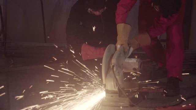 industrial workers cut steel pipes with a metal grinder. - steel stock videos & royalty-free footage