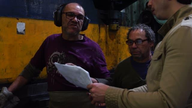 vidéos et rushes de travailleurs industriels discuter de stratégie - amérique du sud