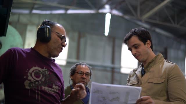 stockvideo's en b-roll-footage met industriële werknemers bespreken strategie - productielijn werker