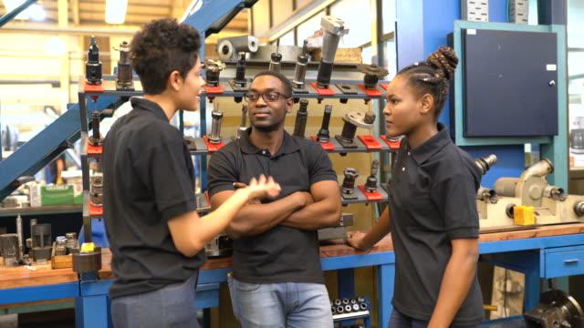 industriarbetare diskuterar arbete på fabriksgolvet - ta en paus bildbanksvideor och videomaterial från bakom kulisserna