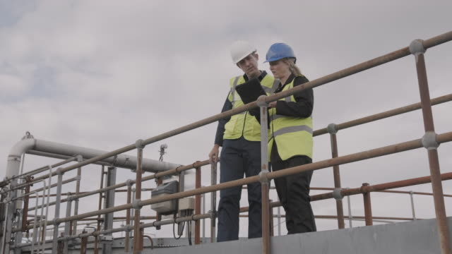 industrial workers inspecting industrial plant using digital tablet technology and wearing protective workwear, low angle view on walkway bridge - quality control stock videos & royalty-free footage