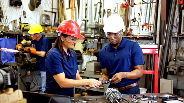 Industrial workers, machinists order parts online together in factory.