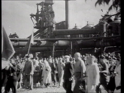 ws industrial workers parading back to factory with banners and flower bouquets/ ms la people standing on height with flag/ ws men standing at... - blast furnace stock videos & royalty-free footage
