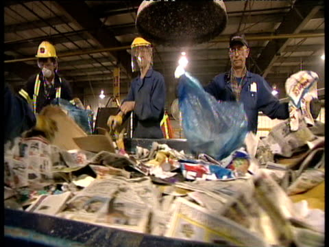 industrial workers sorting through waste paper on conveyor belt at recycling plant - edmonton stock videos and b-roll footage