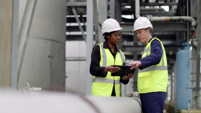 vidéos et rushes de industrial workers using a digital tablet on site - industrie du pétrole