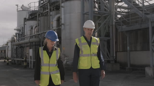industrial workers walking and inspecting industrial plant wearing protective workwear - industry stock videos & royalty-free footage