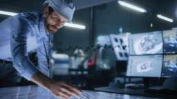 Industry 4.0 Modern Factory Office Meeting Room: Handsome Male Engineer Wearing Hardhat, Uses Pen on Touchscreen Digital Table to Correct, Draw Machinery Blueprints. High-Tech Electronics Facility