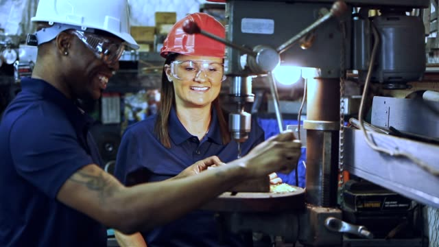Industry: Male and female workers at drill press