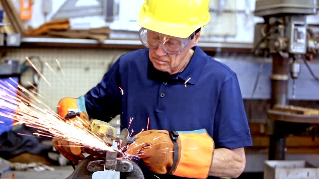 Industry: Man grinding in workshop wearing hardhat and gloves.  Sparks.