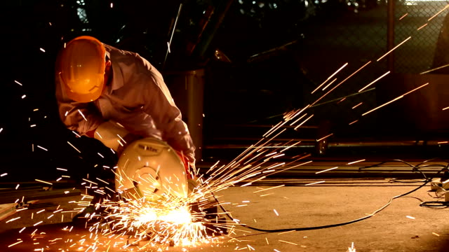 industry worker cutting steel pipe by metal grinder with lighting sparks - steel worker stock videos & royalty-free footage