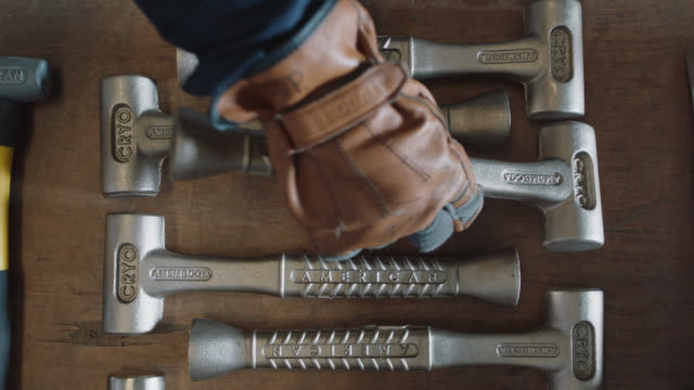 vídeos y material grabado en eventos de stock de cu industry worker removes and then replaces a steel hammer in a group of identical hammers - enfoque de objetos sobre la mesa