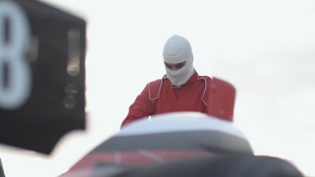 vídeos de stock, filmes e b-roll de ms indy type racing car driver putting on racing helmet / orlando, florida, united states - capacete equipamento