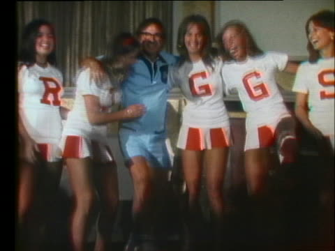 infamous male chauvinist bobby riggs goofs off with a group of cheerleaders. - ビリー・ジーン・キング点の映像素材/bロール